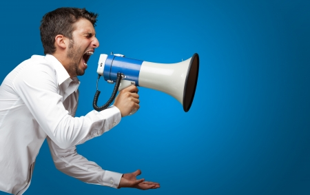 Retrato de un hombre gritando en un megáfono sobre fondo azul
