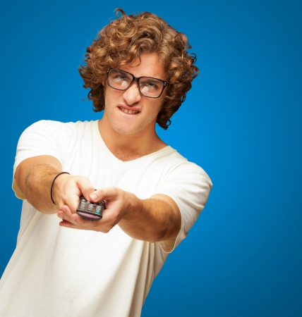 changing channel: Portrait Of Young Man With Glasses Changing Channel With Tv Control On Blue Background