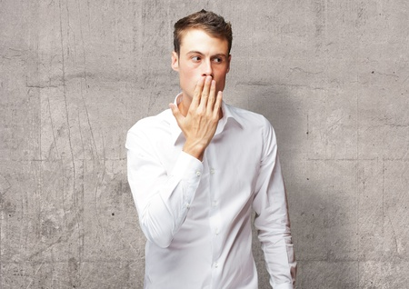 Portrait Of Young Man Covering His Mouth With Hand, Indoor photo