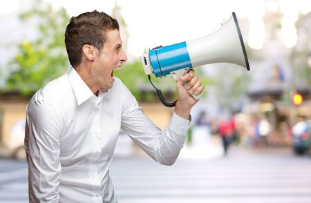 Portrait Of Young Man Shouting On Megaphone, Outdoor photo