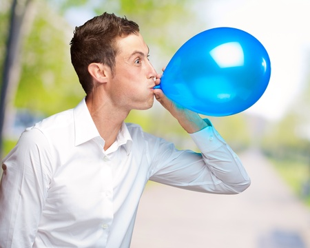 Portrait Of Young Man Blowing A Balloon, Outdoor photo