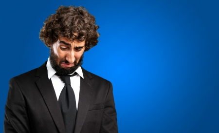 Portrait Of An Unhappy Businessman against a blue background Stock Photo - 16672520