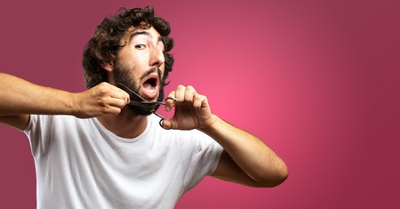 ugly mouth: Man Cutting Beard against a pink background