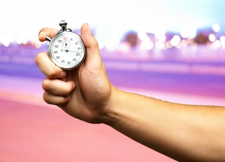Close Up Of Hand Holding Stopwatch at a city by night Stock Photo
