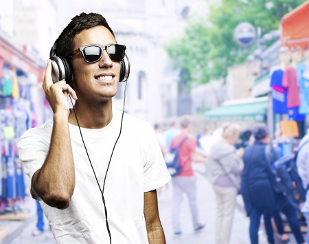 portrait of a young boy listening to music against a street background photo