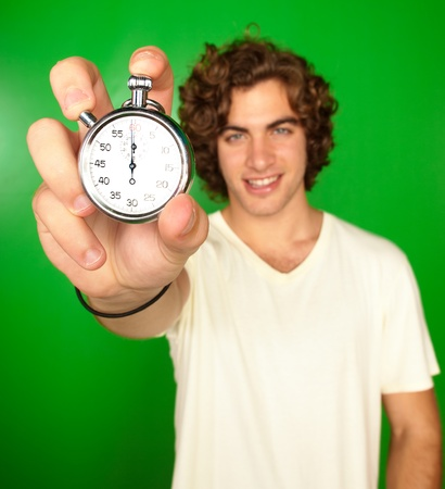 stop time: Man Holding Stopwatch On Green Background