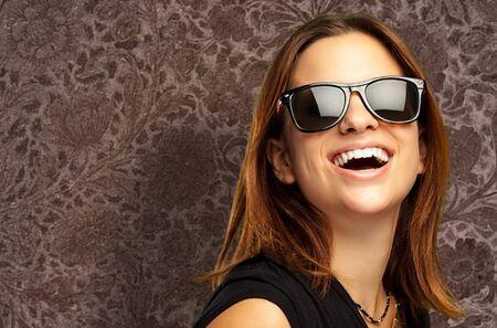 fashionable sunglasses: Portrait Of Happy Woman against a vintage background Stock Photo
