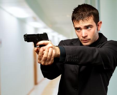 aiming: Man Holding Gun, indoor Stock Photo