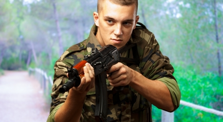 Portrait Of A Soldier Aiming With Gun at a forest Stock Photo - 16672367