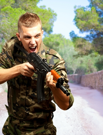 Portrait of an angry soldier aiming at a forest Stock Photo - 16672487