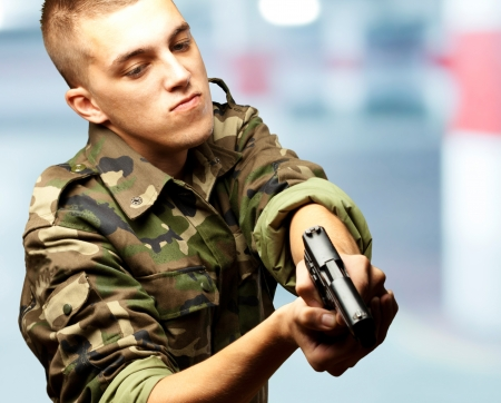 portrait of a serious soldier aiming in a garage photo