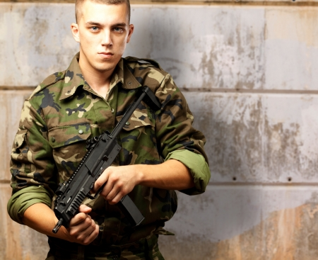 handsome soldier holding gun against an old wall Stock Photo - 16672453