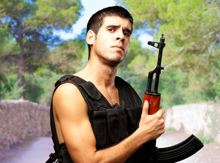 Portrait Of Soldier Holding Gun at a park photo