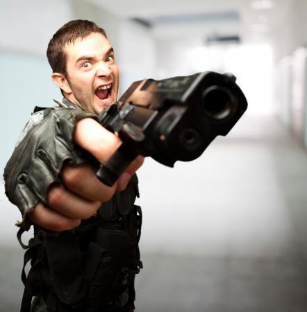 pistola: Soldado enojado sosteniendo la pistola contra un fondo abstracto Foto de archivo