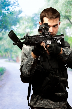 assault rifle: Portrait Of A Soldier Holding Gun at a park