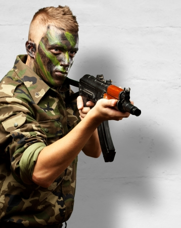 Portrait Of A Soldier Aiming With Gun against a concrete background Stock Photo - 16672424