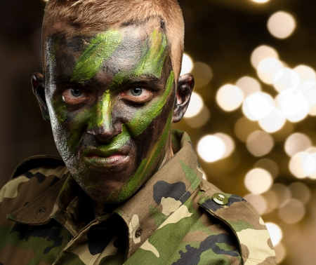 supremacy: Close Up Of Angry Soldier against a background of shiny lights Stock Photo