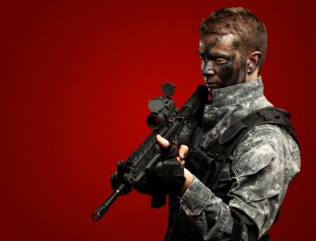 soldado: Retrato del soldado sosteniendo la pistola contra un fondo rojo Foto de archivo