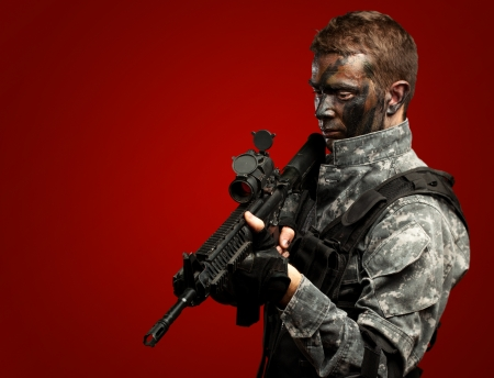 Portrait Of Soldier Holding Gun against a red background