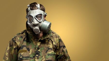 Soldier With Gas Mask against a yellow background photo