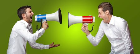 Two Man Shouting On Megaphone On Green Background photo
