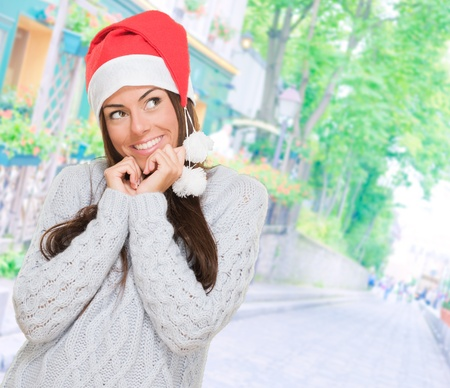 christmas hat: Happy woman wearing a christmas hat against a street background Stock Photo