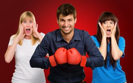 Man With Boxing Gloves And Scared Woman Standing Behind On Red Background photo