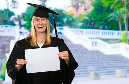 Graduate Woman Holding a blank paper near some stairs, outdoor Stock Photo - 16672421