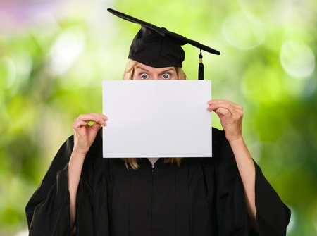 graduate woman hiding behind a blank paper against a nature background Stock Photo - 16672357