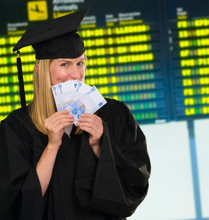 euro banknote: graduate woman holding euro notes at the airport