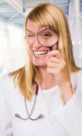 Happy Doctor Looking Through Magnifying Glass, indoor photo