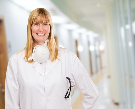 Female Doctor With Protective Mask Around Neck in a passageway photo
