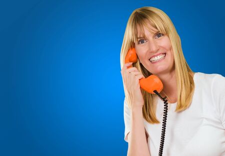 Happy Woman Holding Telephone against a blue background Stock Photo - 16671722