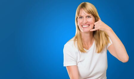 woman holding telephone and doing a gesture against a blue background Stock Photo - 16671755