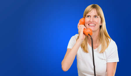 pretty woman talking on telephone against a blue background Stock Photo - 16672345