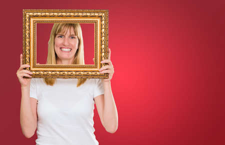 Woman Holding Up A Picture Frame against a red background Stock Photo - 16672414