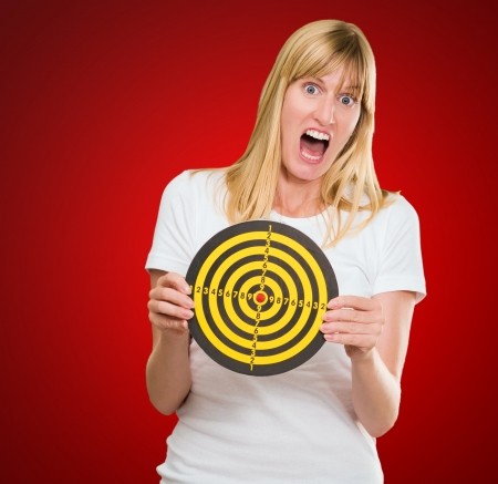 Afraid Woman Holding Dartboard against a red background Stock Photo - 16671746