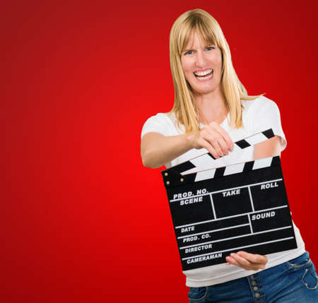 Happy Woman Holding Clapper Board against a red background Stock Photo - 16672341
