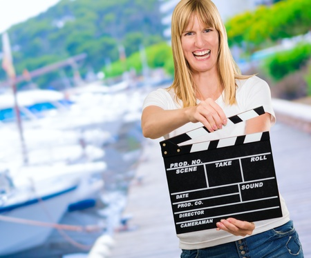 Happy Woman Holding Clapper Board at a port Stock Photo - 16672431