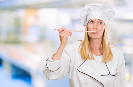 Female Chef Tasting Food against an abstract background Stock Photo - 16672352