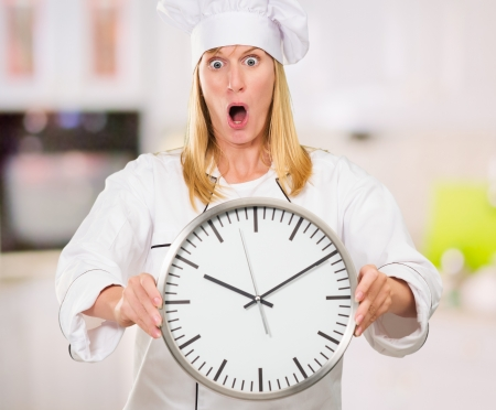 Shocked Female Chef Holding Clock in a kitchen, indoor Stock Photo - 16671742