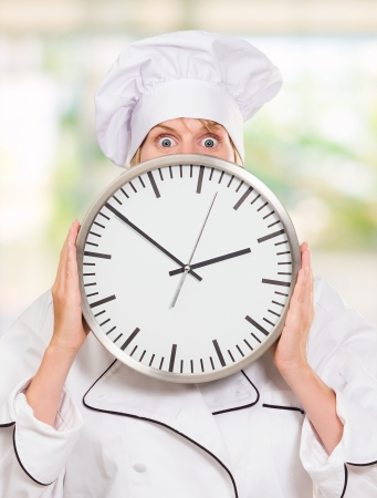 worried chef hiding behind a clock, outdoor Stock Photo - 16671726