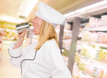 Female Chef Holding Tin Shouting  in a supermarket photo