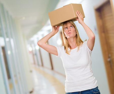 woman holding a box on her head in a passage way photo