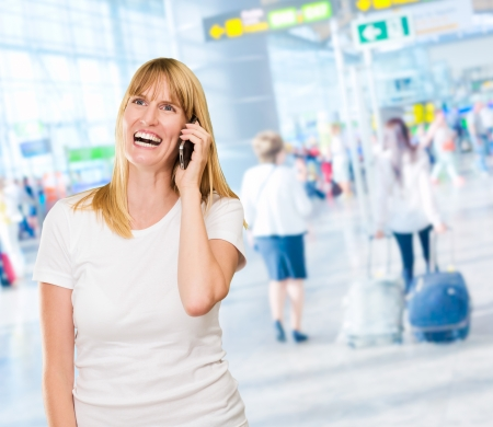 Woman Talking On Cell Phone in an airport Stock Photo - 16672457