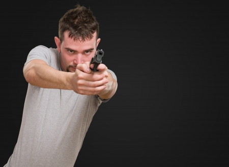 serious man ponting with gun against a black background Stock Photo - 16672393