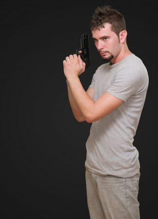concentrated man holding gun against a black background photo