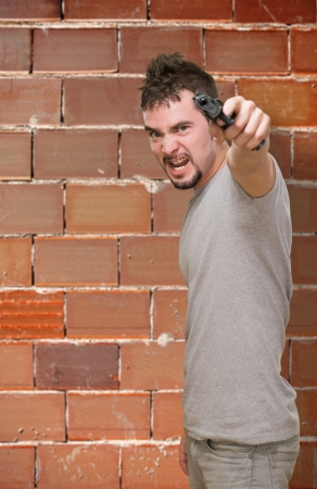 furious man pointing with gun against a brick wall photo