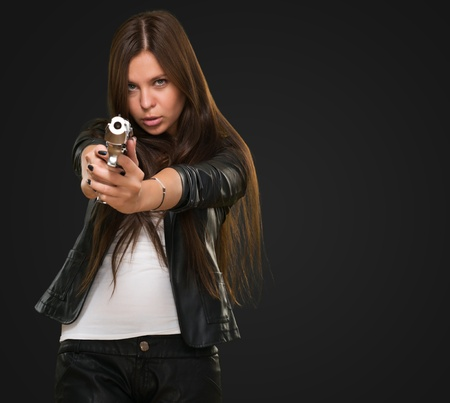 unsatisfied: Portrait Of A Woman Holding Gun against a black background Stock Photo
