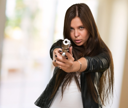 gun room: Portrait Of A Woman Holding Gun against an abstarct background Stock Photo